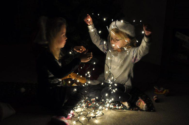 dochters in de weer met kerstlampjes