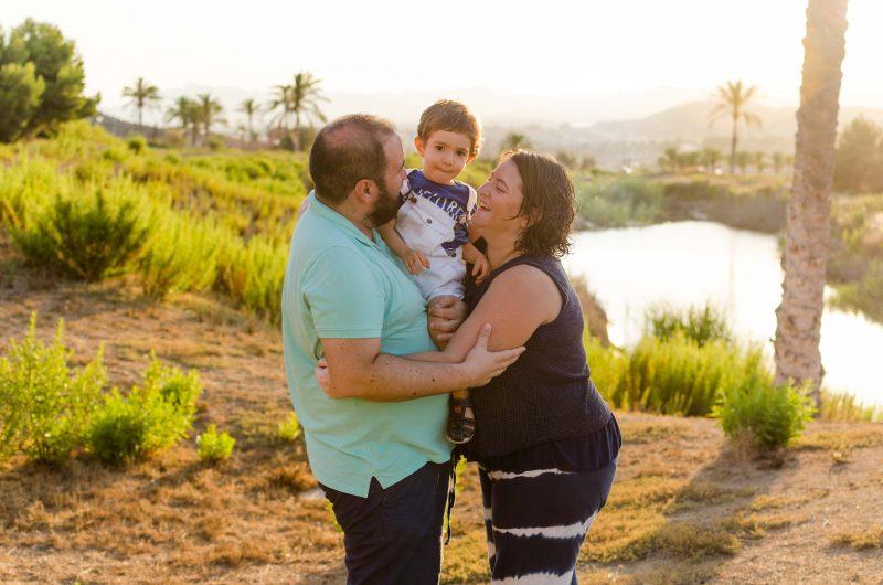 Plano americano de una familia de tres. Están en un campo con un lago al atardecerPapá tiene en brazos al niño. Mamá y papá se están abrazando y están mirando a su hijo. El niño está mirando sereno a cámara.
