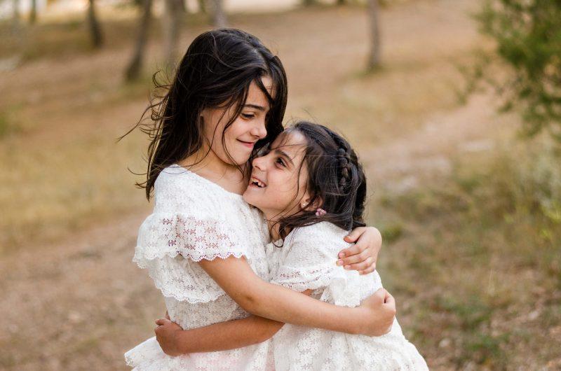 Dos hermanas están abrazadas mirándose la una a la otra y sonriendo. El viento les mueve el pelo. Están en medio del monte, les rodean tonalidades marrones.