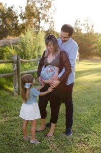 Fotografía de una familia de tres: papá, mamá embarazada y niña. Están los tres de pie en un jardín al atardecer con árboles detrás y una valla de madera a la izquierda de la fotografía. A la niña se la ve de perfil casi de espaldas, está tocando la barriga de su mamá, que la tiene frente a ella. Tanto mamá como papá están mirando a la niña. Papá está detrás de mamá abrazándole la barriga