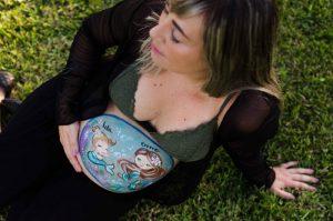Mamá embarazada con la barriga pintada por Colorehadas. El dibujo es de dos sirenas que representan a la bebé de dentro de la barriga y a su hermana de 4 años. La fotografía está hecha desde arriba y la mamá tiene los ojos cerrados y está sintiendo a su bebé.