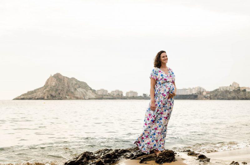 Fotografía de una mujer embarazada de pie sobre unas rocas a la orilla de la playa. Se acaricia la barriga y sonríe. El viento le mece el vestido y el pelo