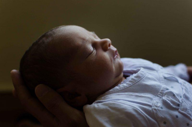 Primer plano de un bebé dormido con la cabeza sobre las manos de su papá.