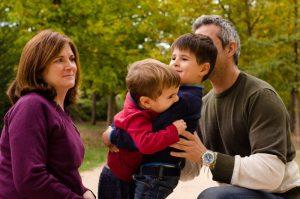 Dos hermanos se abrazan mientras los padres, a su lado, los contemplan sonrientes