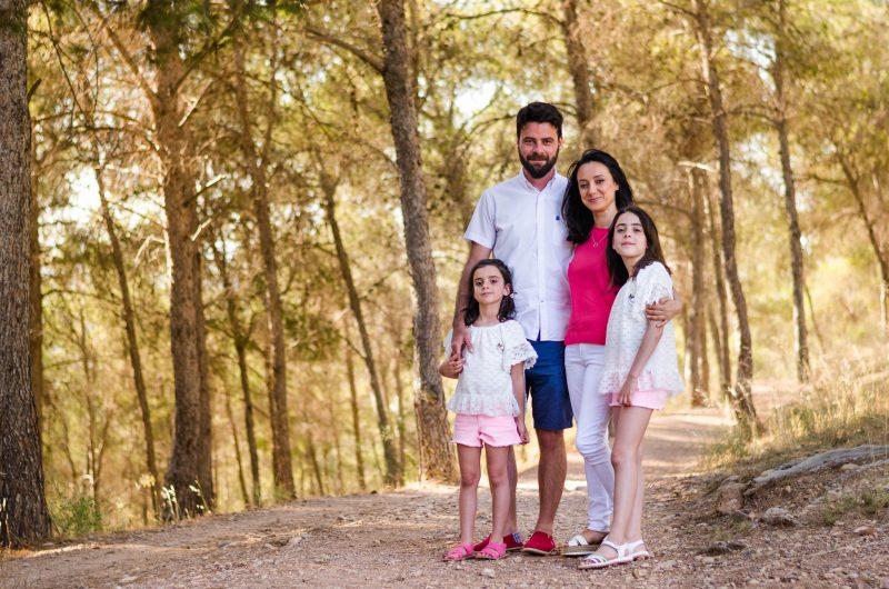 Fotografía posada de una familia compuesta por los padres y dos hijas, todos conjuntados con el blanco y el rosa como colores principales. Los cuatro están posando en un camino en medio del bosque al atardecer