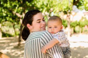 Fotografía de una mamá con su bebé en brazos. La mamá está de espaldas aunque un poco de perfil y se le ve el lateral de la cara mirando a su bebé. El bebé está mirando hacia la fotógrafa y se agarra a la camisa de su mamá con el brazo izquierdo. Están en el Jardín de la Seda
