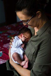 Fotografía de perfil de una mamá que tiene a su bebé en brazos. Es recién nacido y le cabe en un antebrazo. El bebé se arrebuja contra ella.