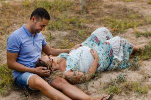 Fotografía de una pareja en medio de un campo seco. Él está sentado y ella está tumbada con la cabeza sobre las piernas de él. Se miran y se sonríen. Él juega con su pelo y ella se acaricia la barriga porque está embarazada