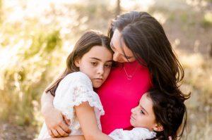 Fotografía de una mamá con sus dos hijas en El Valle de Murcia. La mamá y la niña mayor están fotografiadas de cintura hacia arriba y la niña pequeña desde los hombros hacia arriba. La niña mayor tiene cara triste y se abraza a su mamá en busca de consuelo. la mamá la está mirando y la arropa. Mientras tanto, la hija pequeña se abraza a ellas para animarlas.