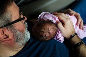 Fotografía a color de un papá y su bebé recién nacido. El papá está sentado y tiene al bebé encima de su pecho tumbado boca abajo. La fotografía está hecha desde arriba y se ve, a la izquierda de la imagen, el perfil del papá y, en la parte central y derecha a su bebé desde la coronilla y acariciado en la espalda por la mano del papá. Fotografía hecha en el Hospital Quirón de Murcia