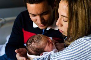 Fotografía a color de una mamá con su bebé recién nacido en brazos y el papá al lado. Ambos miran preocupados a su bebé porque éste está llorando. El papá acerca una mano al bebé por la espalda para intentar calmarlo. Fotografía tomada en el Hospital Virgen de la Arrixaca de Murcia