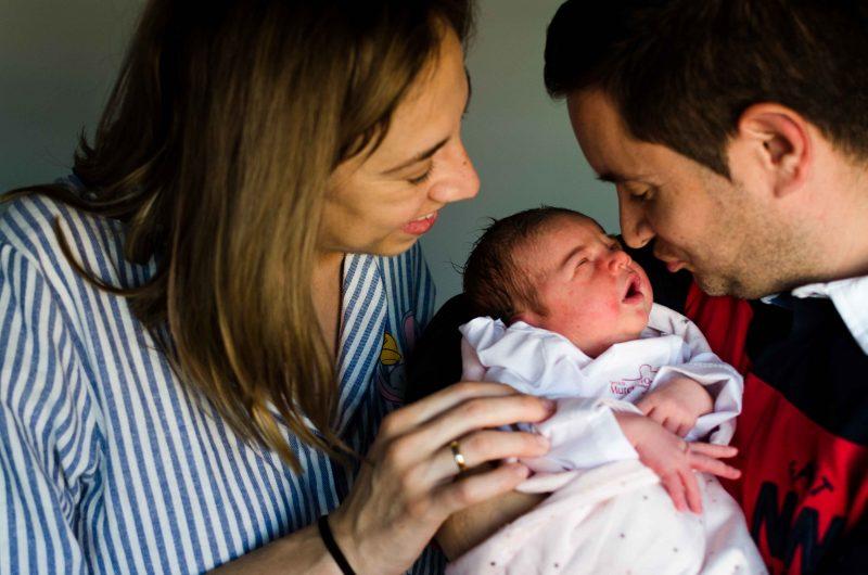 Fotografía a color de un papá con su bebé recién nacido en brazos y una mamá a su lado bien cerca acariciando a su bebé y sonriendo a ambos. Papá va a darle un beso a su bebé y parece que el bebé intenta abrir los ojos para reconocerlo. Fotografía tomada en el Hospital Virgen de la Arrixaca de Murcia.