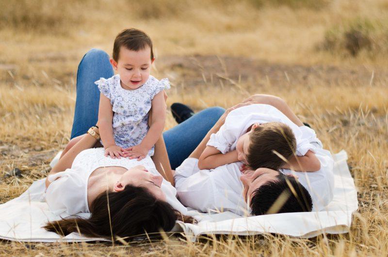 Fotografía de una familia tumbada sobre un campo marrón. Los padres están tumbados boca arriba y se miran. El hijo está tumbado boca abajo encima de su papá y la niña está sentada encima de la barriga de su mamá.
