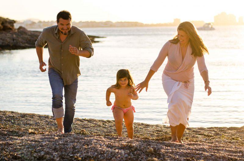 Imagen de una familia compuesta por papá, mamá e hija. Los tres están en la playa al atardecer, con el mar detrás de ellos y corriendo hacia la cámara. Mamá mira hacia su hija y le alarga la mano por si la niña la necesita para seguir corriendo. La niña va en el medio de los tres. Los tres sonríen pero no miran a cámara, están centrados en su carrera.
