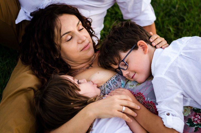 Imagen de una mamá tumbada en el césped de una zona verde de Murcia, con su hijo y su hija encima y apoyada sobre la pierna de papá, a quien no se le ve. Como protagonista de la fotografía está mamá, con los ojos cerrados y abrazando a su hijo e hija. Ella está tomando teta y él está tumbado sobre el otro lateral de ella con los ojos cerrados.