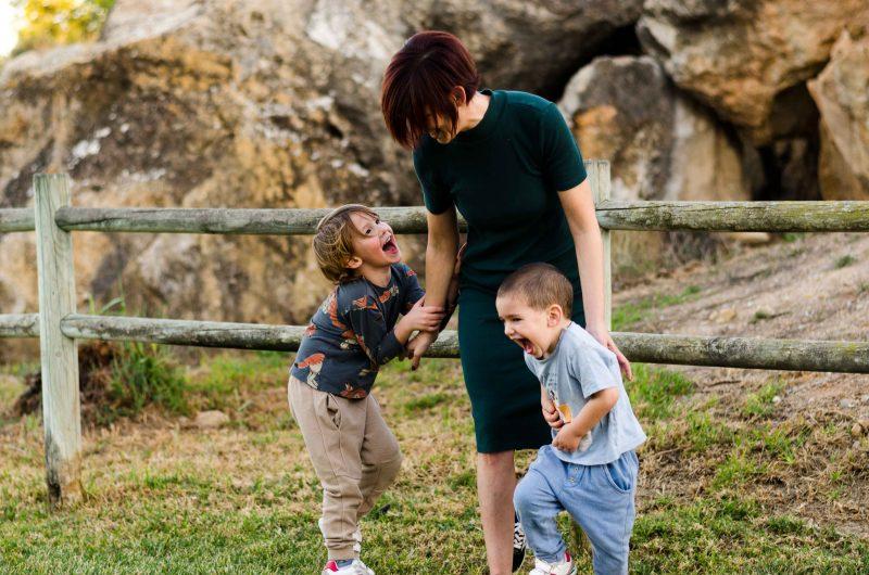 fotografía de una mamá jugando con sus dos hijos de 3 y 5 años. Están en un paisaje natural, detrás de ellos hay una valla de madera y después una zona rocosa. Sobre el suelo hay césped. El hijo mayor está mirando y agarrando a su mamá por el brazo, a la vez que se ríe mucho. El hijo pequeño está muy cerca de su mamá, pero empieza a huir ya que se estaban haciendo cosquillas.