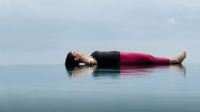 A person practicing Yoga Nidra floating on serene waters
