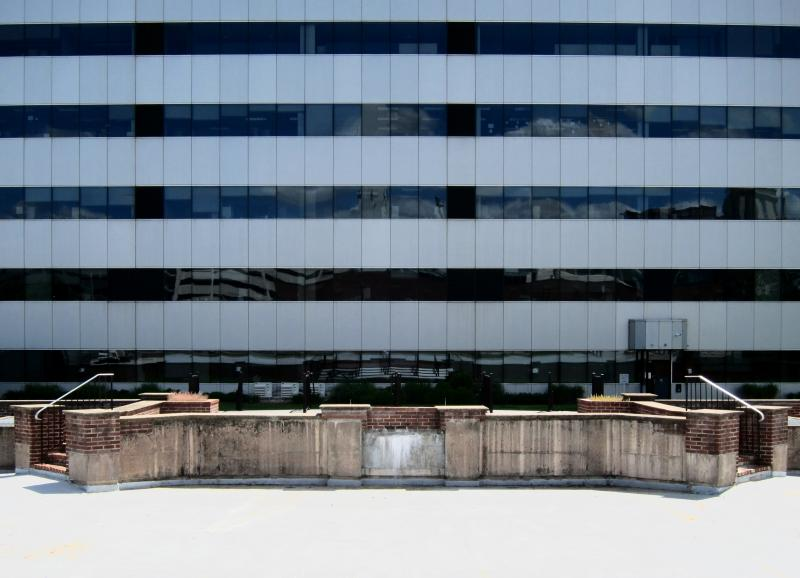 Die Fassade eines Bürogebäudes mit Reflexionen und zwei spieglebildlichen Treppenaufgängen ins Nichts