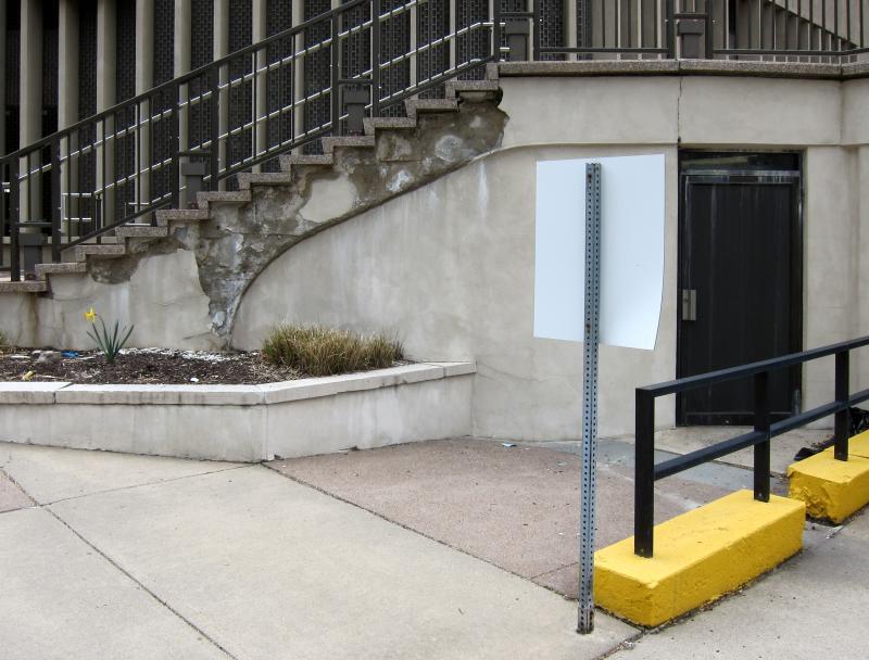 Eine einsame Osterglocke vor dem bröckelnden Beton einer Treppe, rechts davon die weiße Rückseite eines Schilds sowie eine braune Tür, ein braunes Geländer