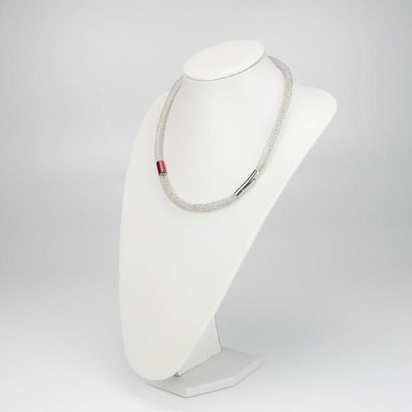 Schlauchkette aus Edelstahldaht mit einem Durchmesser von 10 mm. Das rote Aluminiumröhrchen wurde darübergezogen, ist also beweglich und 15 mm lang. Verschlossen wird die Kette mit einem Magne-Steck-Verschluss aus Edelstahl.