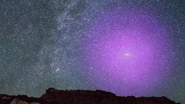 Esta ilustración muestra el halo gaseoso de la galaxia de Andrómeda si pudiera verse a simple vista. A una distancia de 2,5 millones de años luz, la majestuosa galaxia espiral de Andrómeda está tan cerca de nosotros que aparece como una mancha de luz en forma de cigarro en lo alto del cielo otoñal. Si su halo gaseoso pudiera verse a simple vista, sería aproximadamente tres veces el ancho que la Osa Mayor, fácilmente la característica más grande del cielo nocturno. Credits: NASA, ESA, J. DePasquale y E. Wheatley (STScI) y Z. Levay (imagen de fondo)