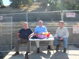 Spectators have doughnuts and orang juice while watching the train car move -- Vic Stewart Restauranteur John Herrington on Left, a friend, and John Curtis