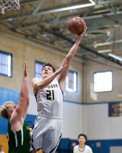 Brody Eglite soars to the basket as Capuchino's Kenny Osterfund defends