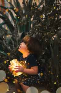 child holding clear glass jar with yellow light