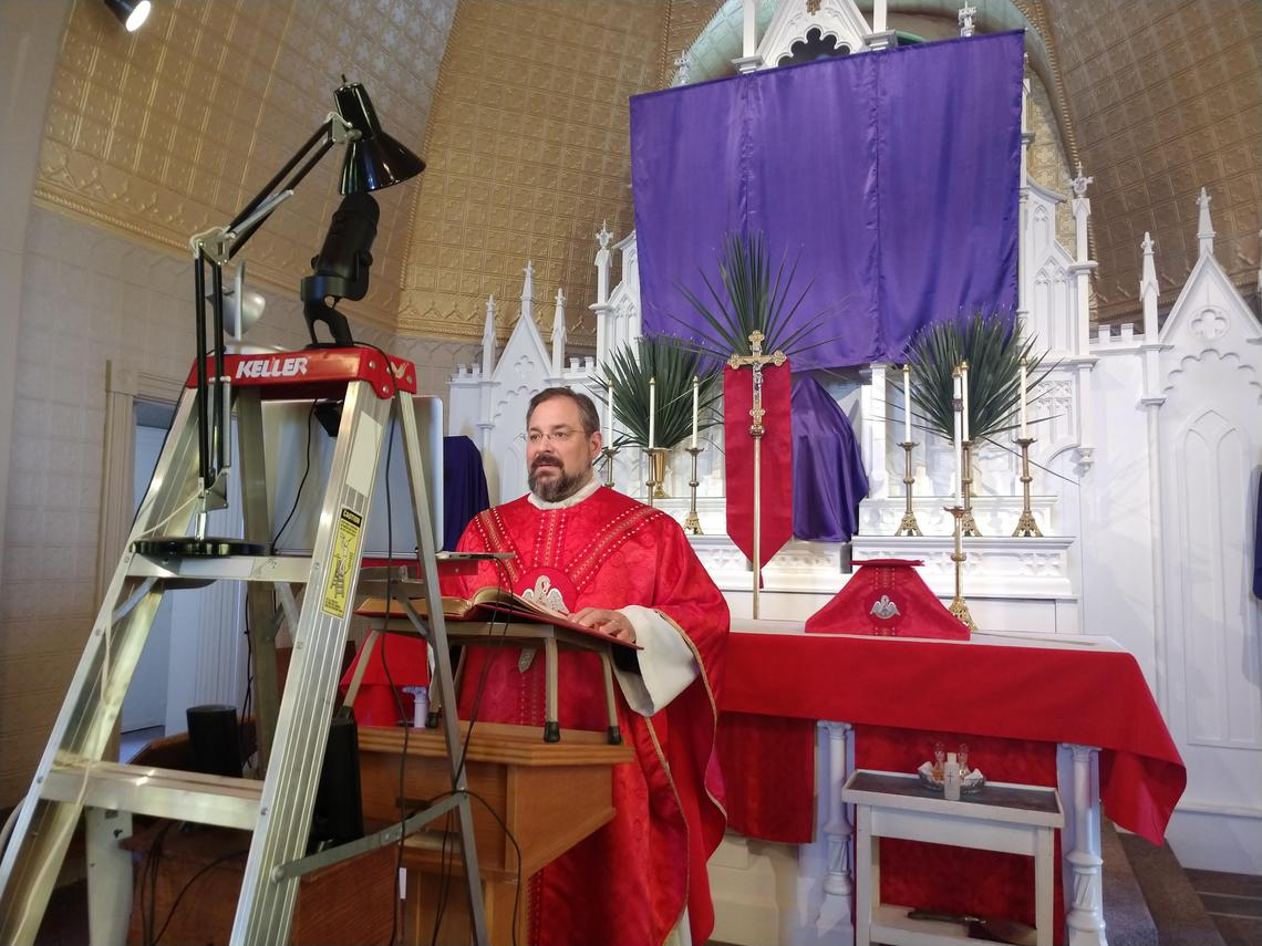 Father Jason Lefor films the Palm Sunday Mass in 2020 for the St. John Nepomucene website and Facebook page. Photo courtesy of Sue Vacek / Special to The Forum