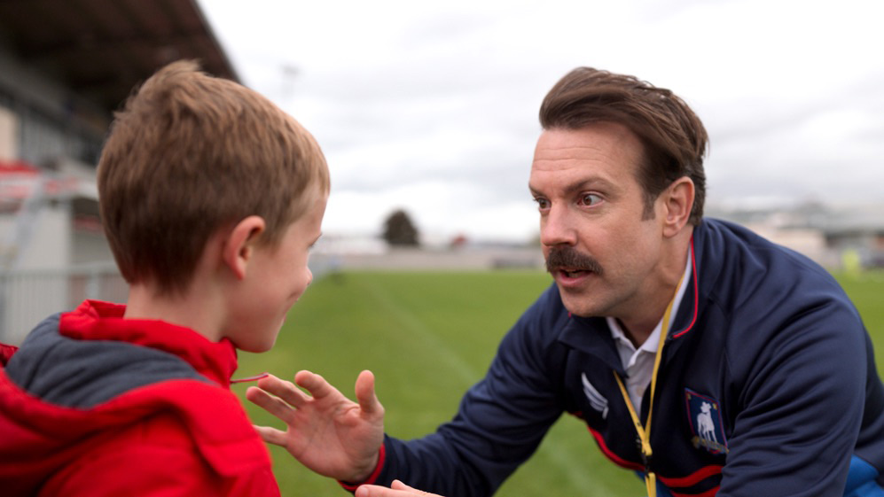 """Jason Sudeikis and Gus Turner in """"Ted Lasso,"""" """"Tan Lines"""" now streaming on Apple TV+."""