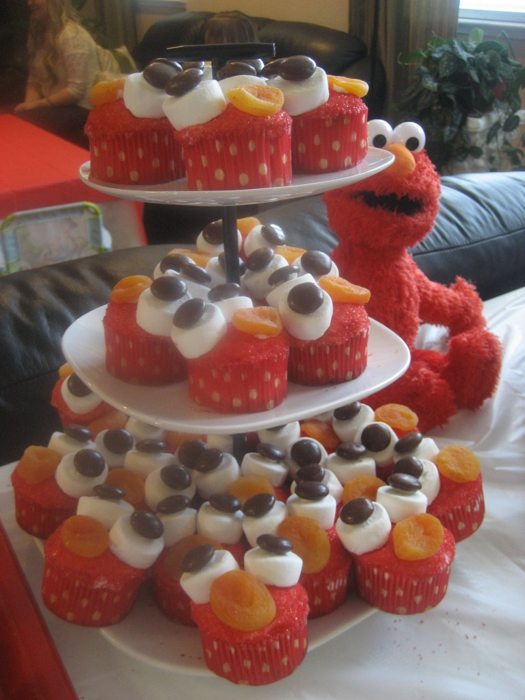 Elmo doll sitting next to a three tiered cake stand covered in Elmo decorated cupcakes