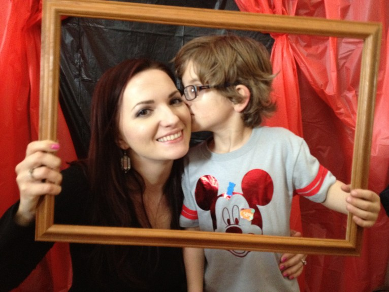 Mom and son in a picture frame. Son is giving kiss to mom on the cheek.