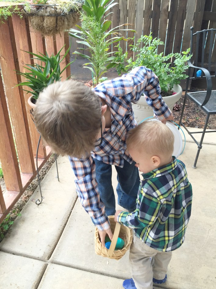 Two boys collecting Easter eggs into a basket