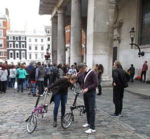 His and her Bromptons, possibly consulting Google Maps in Convent Garden. Taken October 2015, London.