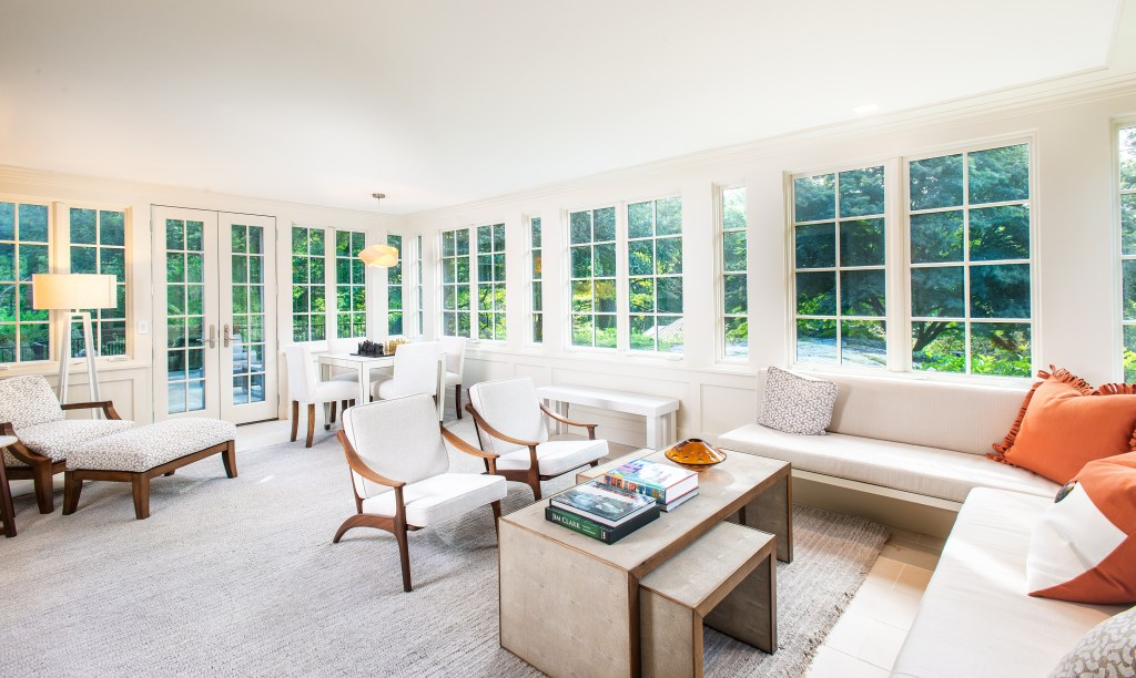 A sunroom with wrap around walls of windows french doors and modern natural wood furniture with white decor on heated floor with area rugs and orange pillows