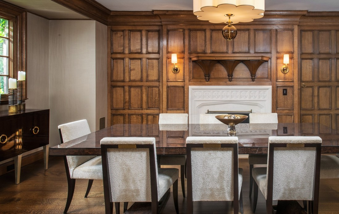 Elegant formal dining room with paneled walls, modern furniture with traditional appeal hardwood floor fireplace mantel and natural light