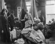 OLIVE EDIS; IWM PHOTOGRAPHER OF THE WOMEN'S SERVICES IN FRANCE 1919 (Q 8046) French civilian women repairing tents using a treadle sewing machine and hand stitching under the supervison of Miss Philpots and Miss Leacock, Queen Mary's Army Auxiliary Corps (QMAAC), No. 8 Ordnance Depot, Abbeville. Copyright: © IWM. Original Source: http://www.iwm.org.uk/collections/item/object/205194671
