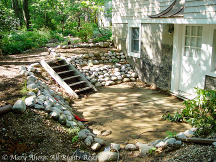 River rock walls with temporary steps reclaimed from the basement