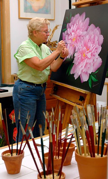 Mary Ahern the artist in her studio painting.