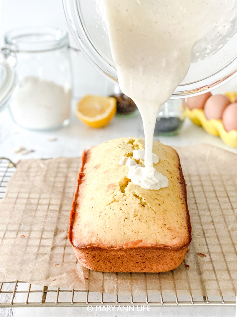 Poppyseed lemon loaf cake recipe with a vanilla bean glaze topped with sliced almonds.