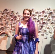 me in front of my work in the dress I designed.
