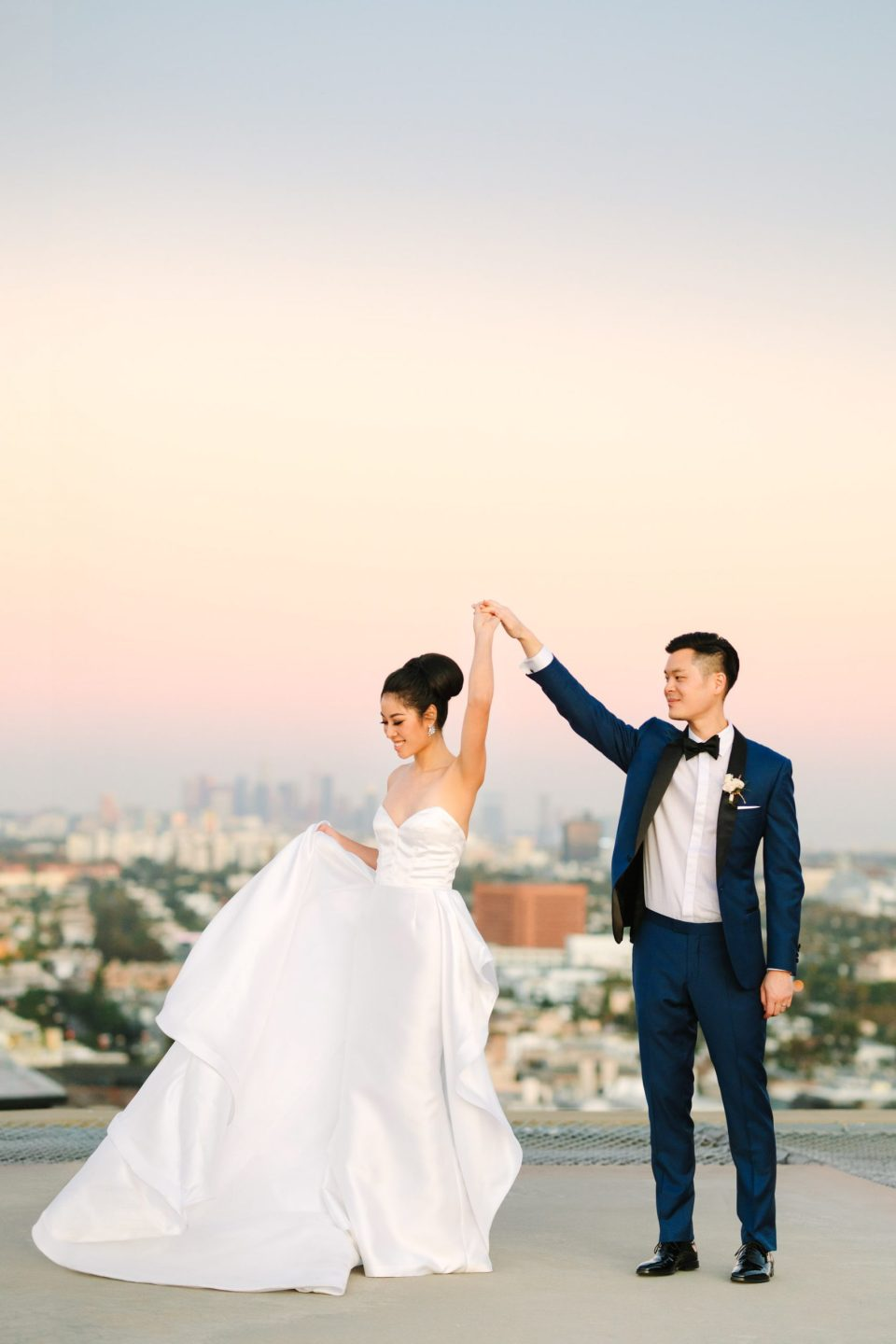 Couple twirling on rooftop in Los Angeles Indian Fusion wedding at Fig House Los Angeles by Mary Costa Photography