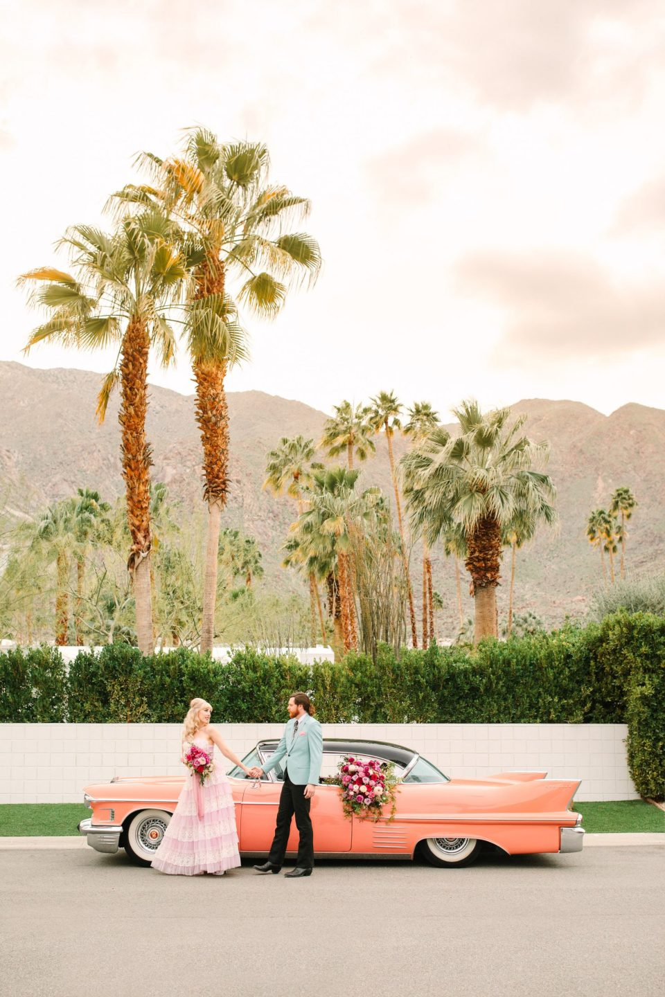 Couple with vintage pink Cadillac by Mary Costa Photography