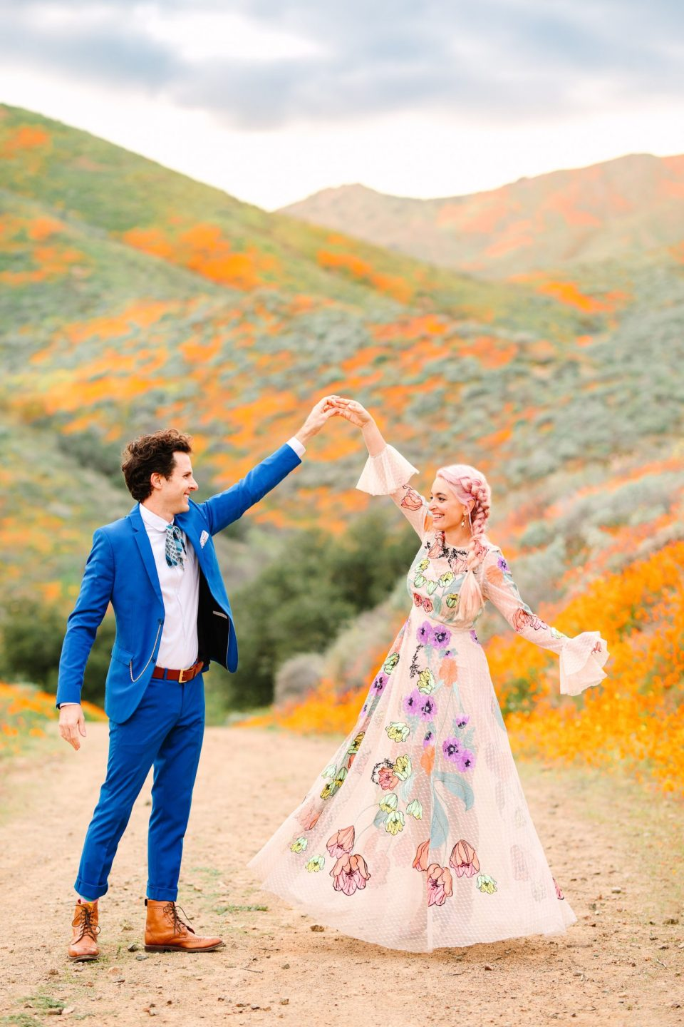 Colorful couple in poppy field by Mary Costa Photography