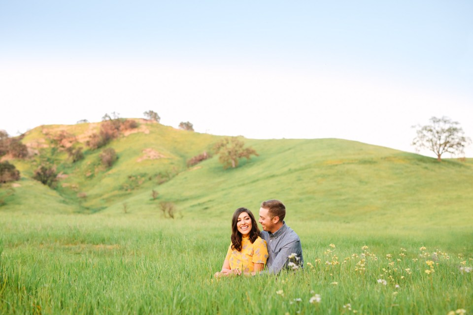 Couple in green rolling field by Mary Costa Photography