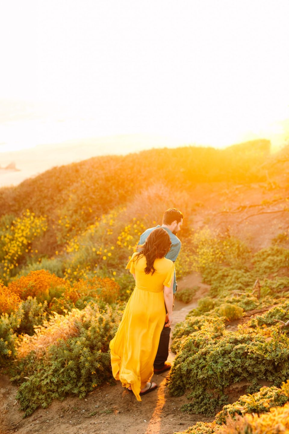 Couple walking to beach in yellow by Mary Costa Photography