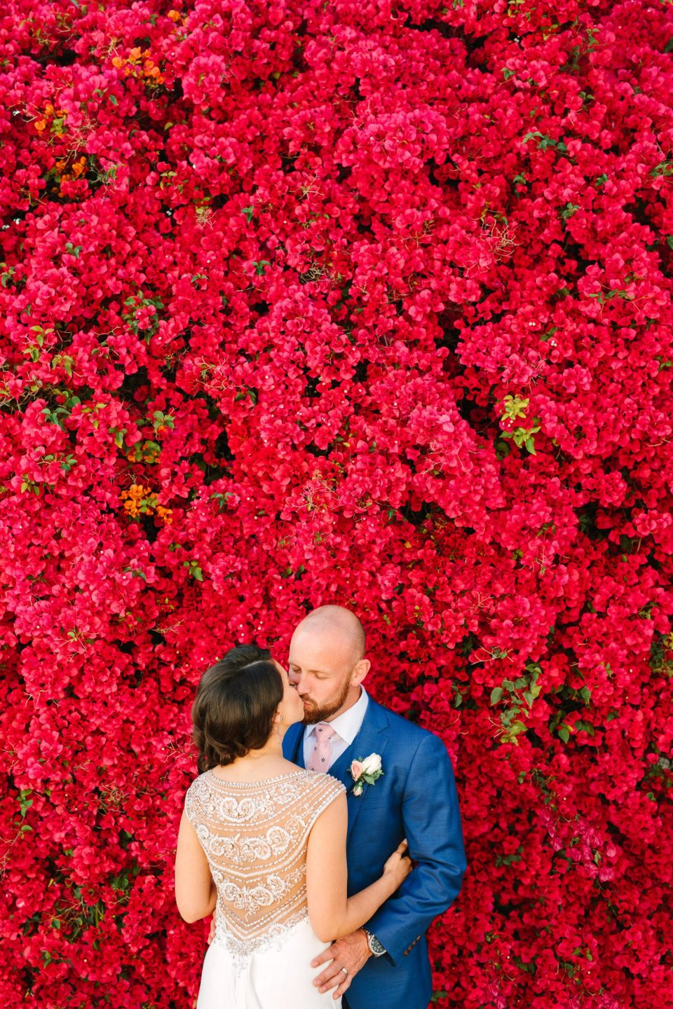 Couple kissing by blooming bougainvillea by Mary Costa Photography