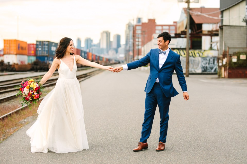Bride and groom twirling with Seattle backdrop by Mary Costa Photography