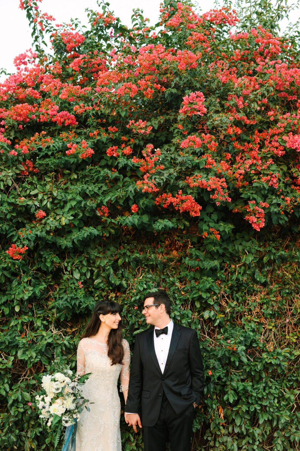 Bride and groom portrait with bougainvillea by Mary Costa Photography