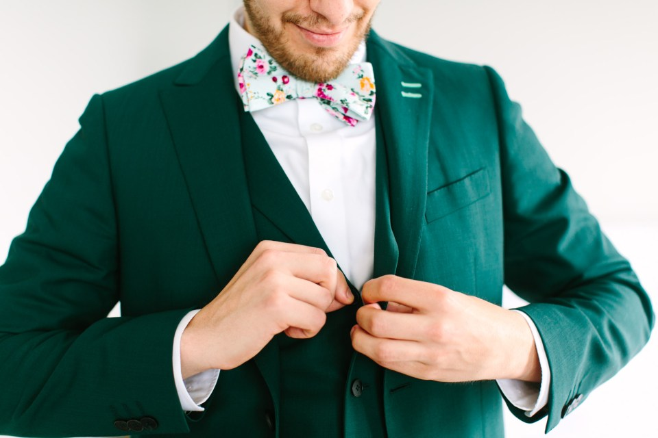 Groom getting ready in emerald tux by Mary Costa Photography
